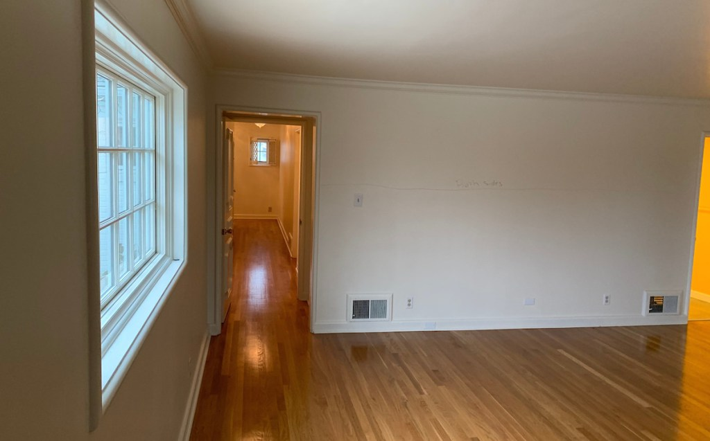 small room with narrow hallways and wood floors