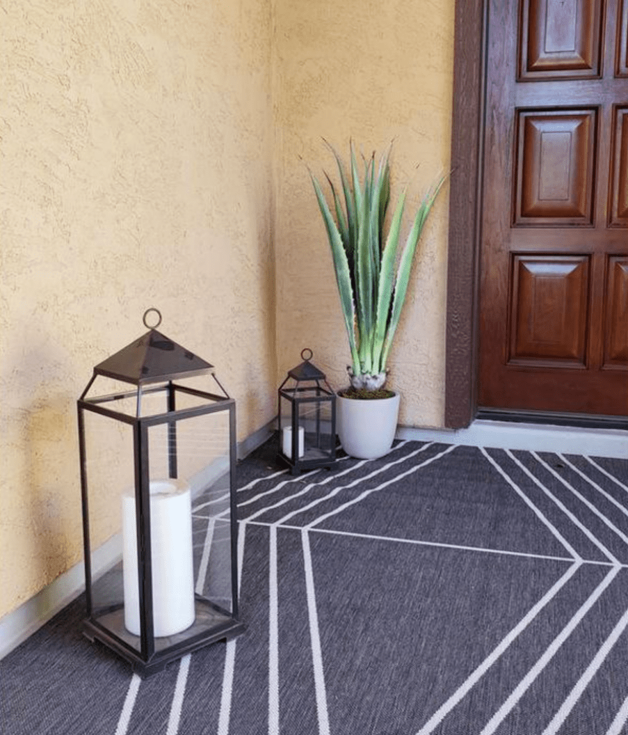 faux plant and candle in entryway by front door