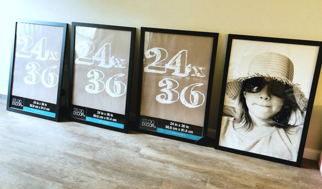 4 black poster frames on the floor