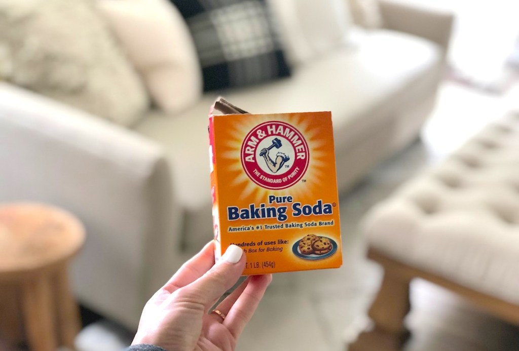 hand holding baking soda in front of couch living room
