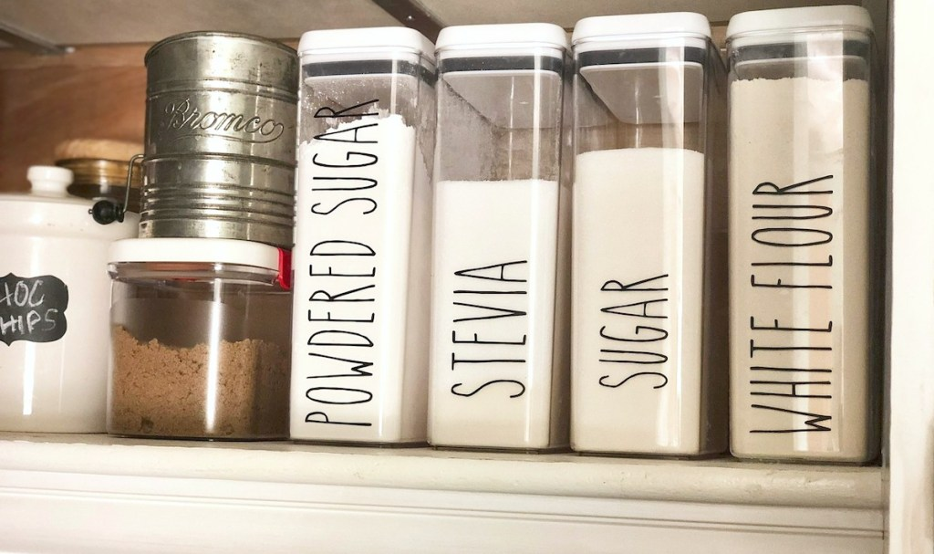 row of white pantry food in clear labeled containers