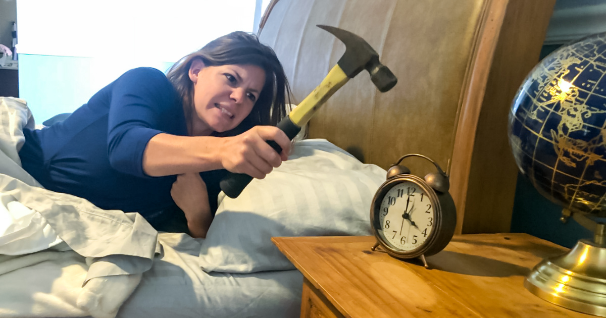 woman using a hammer to hit an alarm clock