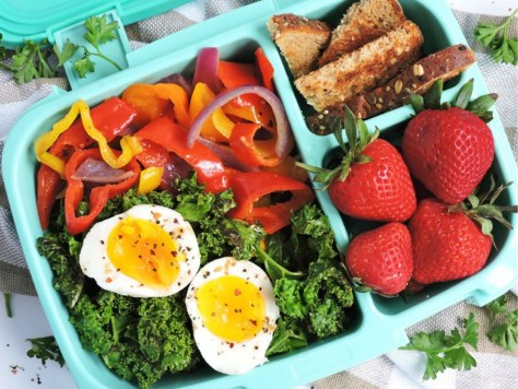 Bentgo Bento container filled with salad, peppers, eggs, strawberries and whole grain bread