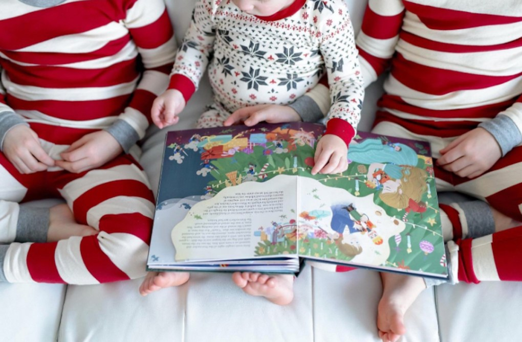 kids holding christmas books wearing red and white holiday pajamas