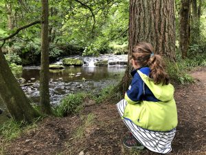 Girl crouched on the banks of a stream at Hardcastle crags
