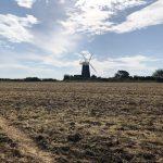 Windmill across a recently cut hay field