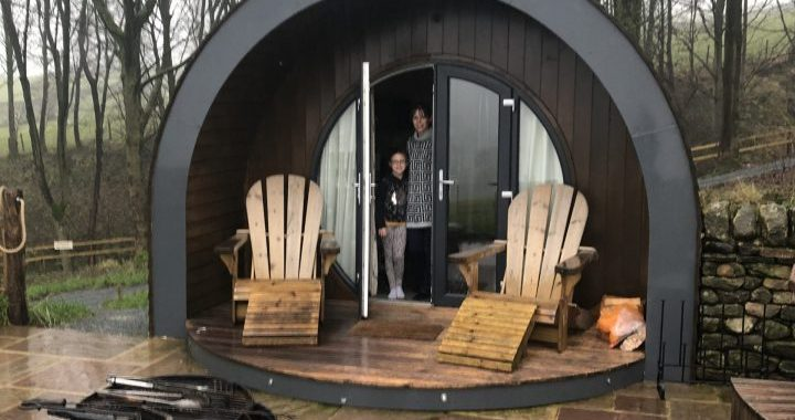 Outside of the glamping pod, hip2trek and little legs stand in pod doorway