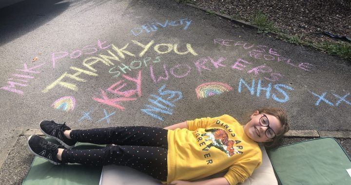 Little legs lies on cushions on a driveway, behind her chalk writing thanking key workers is behind her