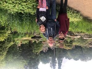Portrait of man and two children stood in rockery garden