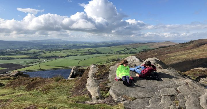 View of the landscape from the top of the crag. Two children lie of the rocks in foreground