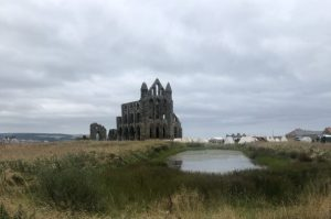 Whitby Abbey and in the foreground a pond infront, tents can be seen to the side of the abbey