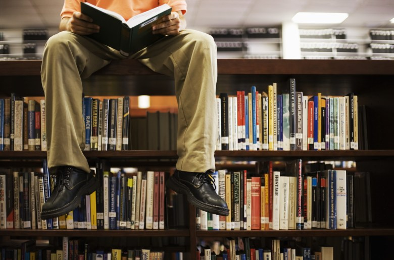 Man Reading Book and Sitting on Bookshelf in Library