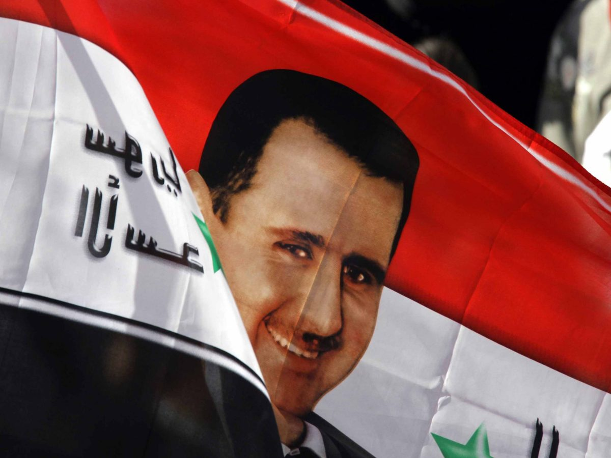 Syrian's wave their national flag with an image President Bashar al-Assad during a rally in his support in the capital in Damascus on November 13, 2011, a day after the Arab League suspends Syria until President Bashar al-Assad implements an Arab deal to end violence against protesters, calling for sanctions and transition talks with the opposition. AFP PHOTO/LOUAI BESHARA (Photo credit should read LOUAI BESHARA/AFP/Getty Images) ORG XMIT: