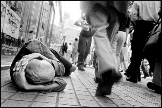 JAPAN. Tokyo. 1999. Homeless man sleeps in the streets while commuters pass by.