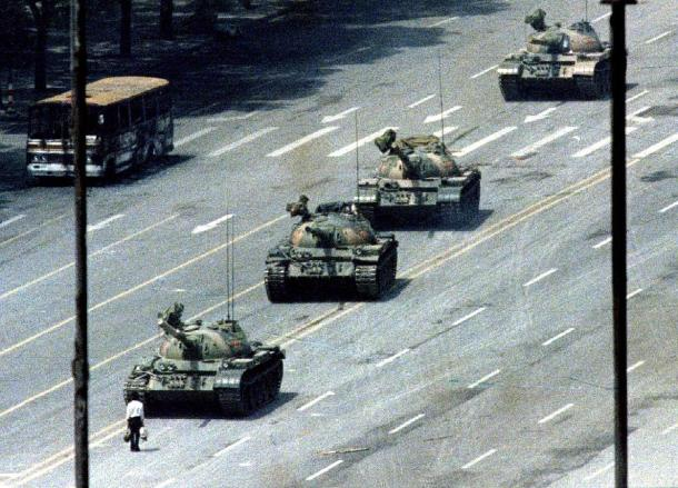 File photo of a Beijing citizen standing in front of tanks on the Avenue of Eternal Peace