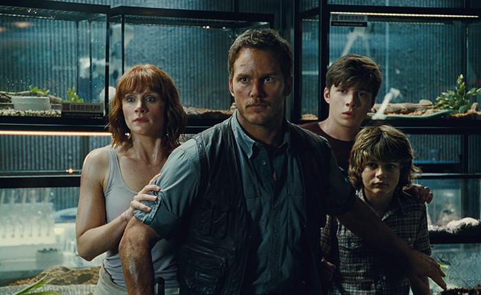 Grupo de personajes protagonistas escapando de las garras de un velociraptor