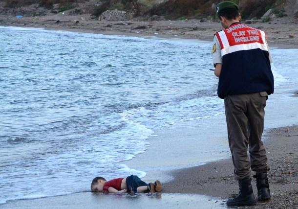 Un policía turco frente a Aylan Shenu, el niño sirio que murió ahogado tras naufragar un barco lleno de refugiados. AFP - Nilufer Demir.