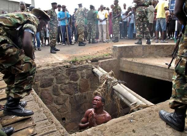 Un hombre pide ayuda a militares tras refugiarse en una cloaca para huir de un linchamiento. AFP - Aymeric Vincenot.