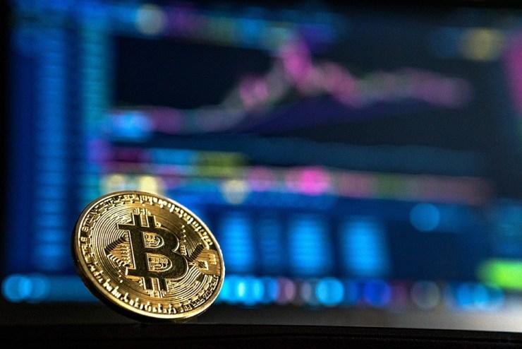 Moneda de Bitcoin con un gráfico de inversión detrás