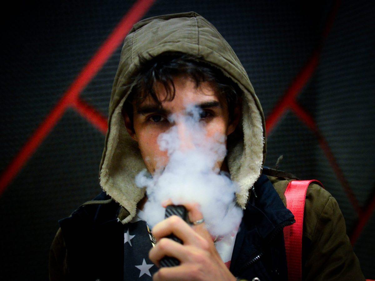 Persona vapeando, vapor del cigarrillo electrónico