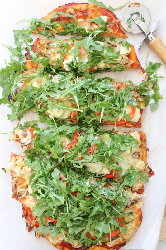 Packed with brussels sprouts, mushrooms, cauliflower, spinach and topped with piles of fresh arugula, this Leek & Mushroom pizza is a veggie lover's dream!
