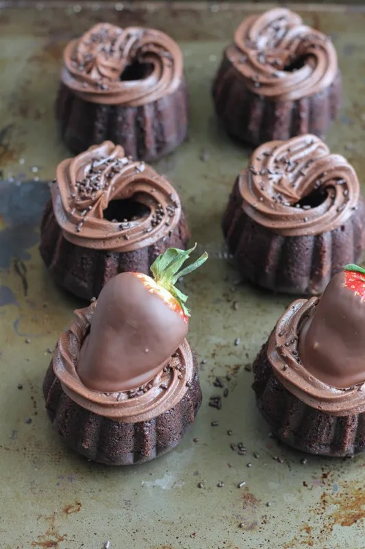 Triple chocolate mini bundt cakes topped with chocolate covered strawberries. The perfect dessert for chocolate lovers. You need these for Valentine's Day!!