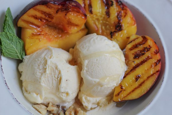 Vanilla ice cream with grilled peaches in a white bowl garnished with mint.