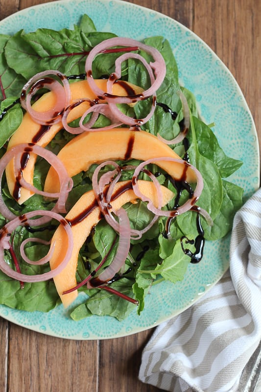Simple Cantaloupe Salad drizzled with balsamic glaze.