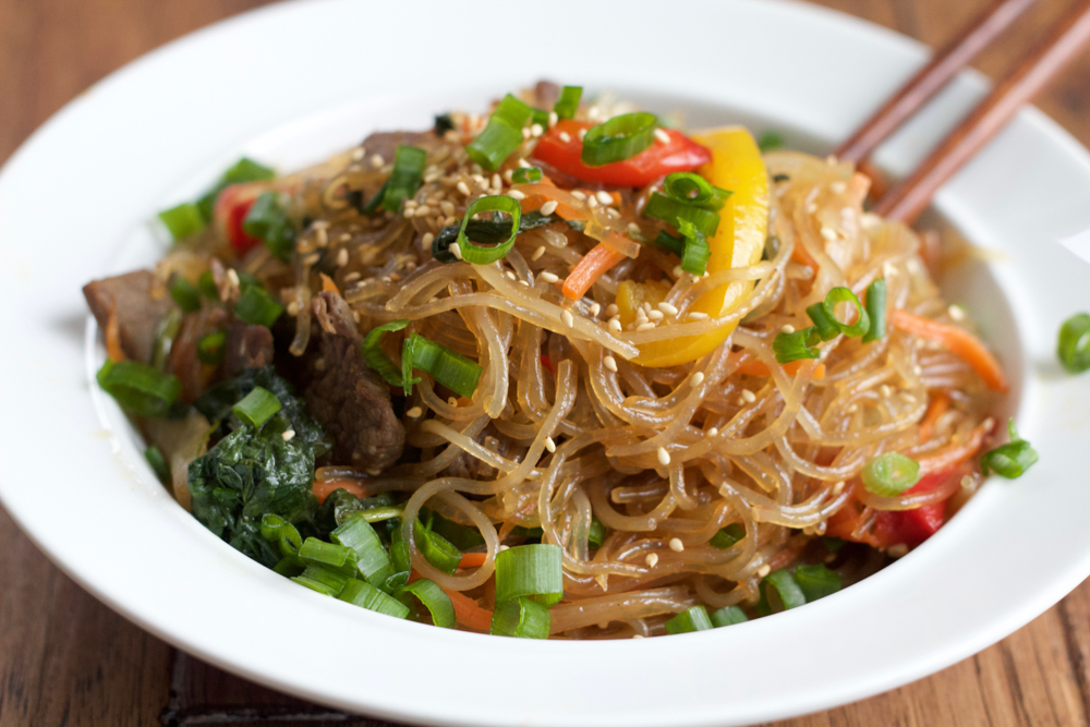 Japchae: Korean Stir Fried Noodles with marinated beef on white plate