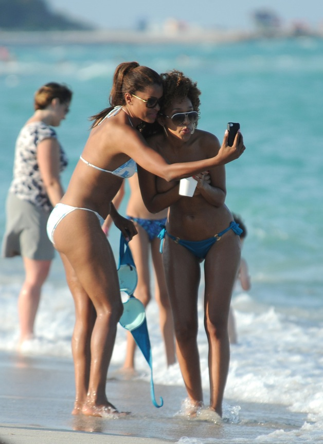 **CONTAINS NUDITY** Claudia Jordan plays around and takes pictures with model friend Aisha Thalia who decides to go toploss while on the beach in Miami