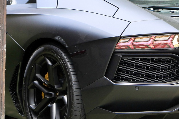 Kanye West's very expensive Lamborghini Aventador shows signs of its mishap that occurred with Kim Kardashian's gate yesterday