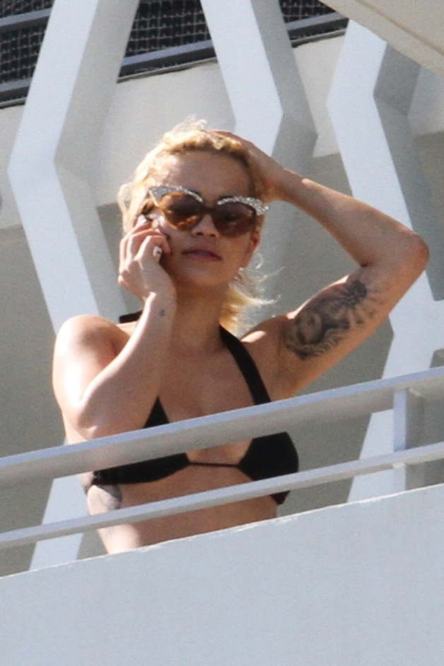 Rita Ora appears to be feeling much better, as she steps out on her Miami hotel balcony in a bikini top