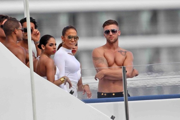 Jennifer Lopez finds herself surrounded by a group of shirtless male models as she films a video on a yacht in Miami