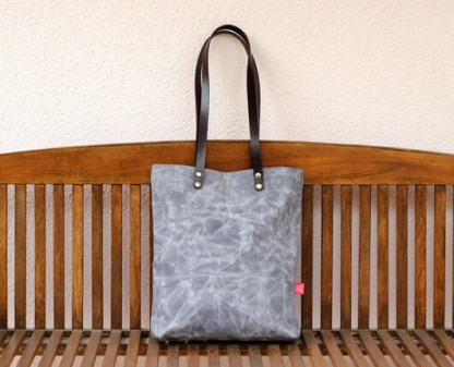 light gray waxed bag with leather strap