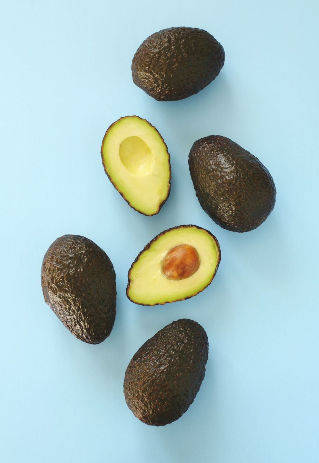 Avocado halves and whole on a blue speckle, top viev.