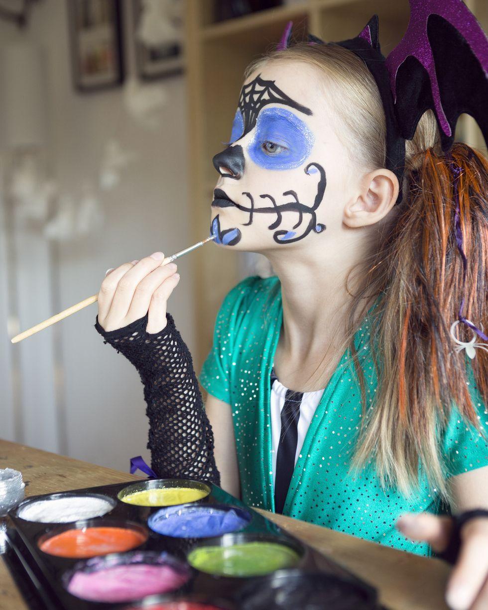 child applying halloween face paints