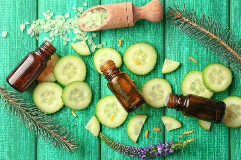 Composition with cucumber essential oils on wooden background, top view
