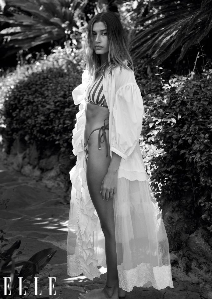 hailey bieber stands in the sand wearing a bikini and sheer dress