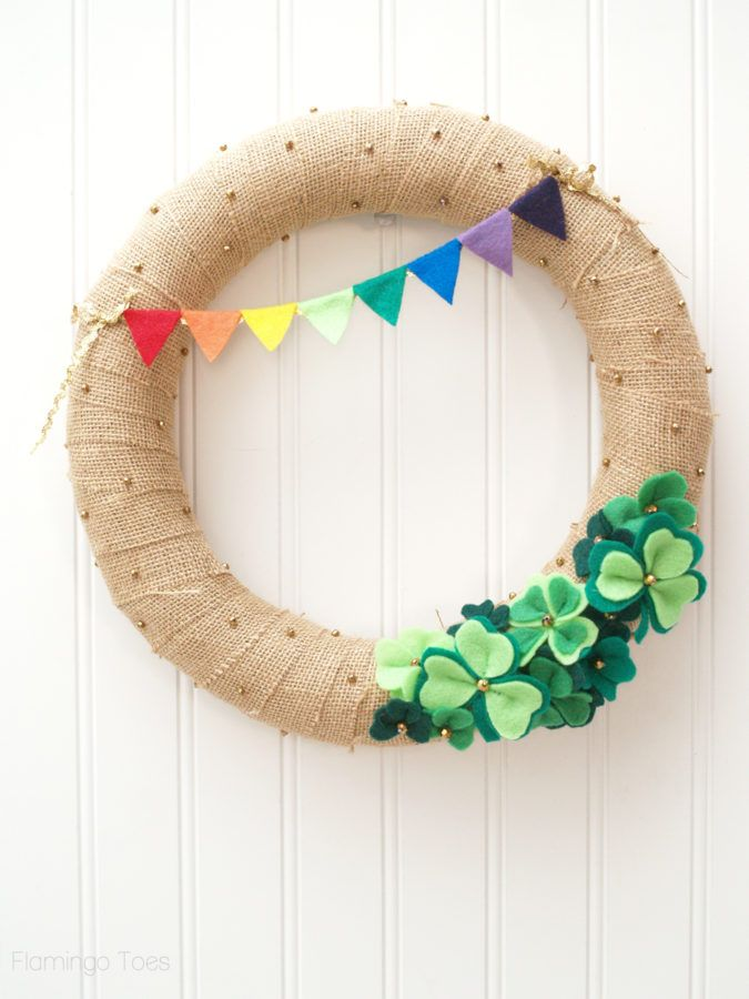 wreath made out of glittery gold burlap with green felt shamrocks at the bottom and a little felt rainbow at the top