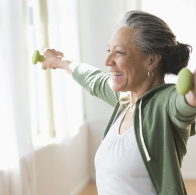 Older Hispanic woman lifting weights in living room
