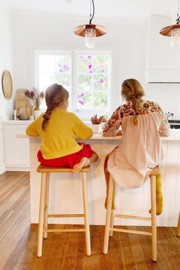 two girls doing homework at kitchen island