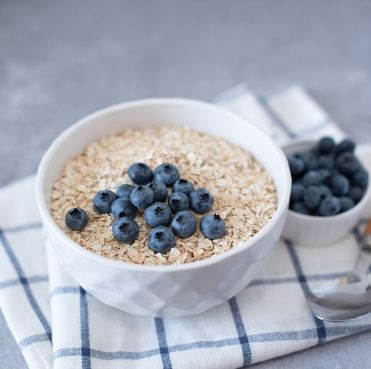 homemade oatmeal with blueberries and strawberries in bowl on gray concrete background healthy breakfast