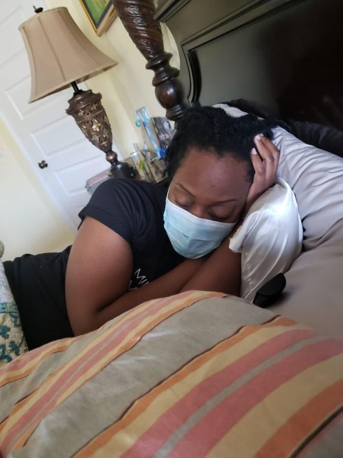 dr jehanne julien banica lays in bed with a face mask on