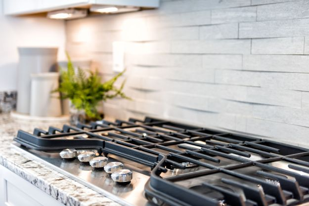 Macro closeup of modern luxury gas stove top with tiled backsplash