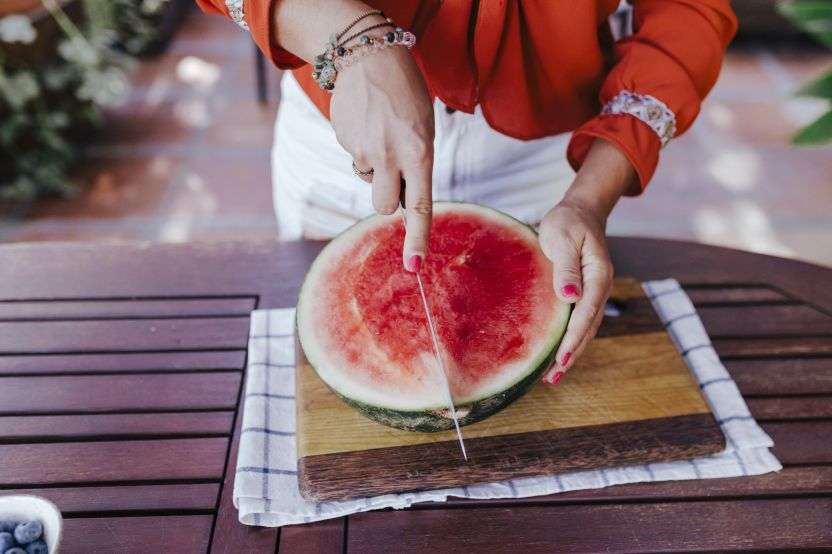 midsection of woman cutting watermelon on table