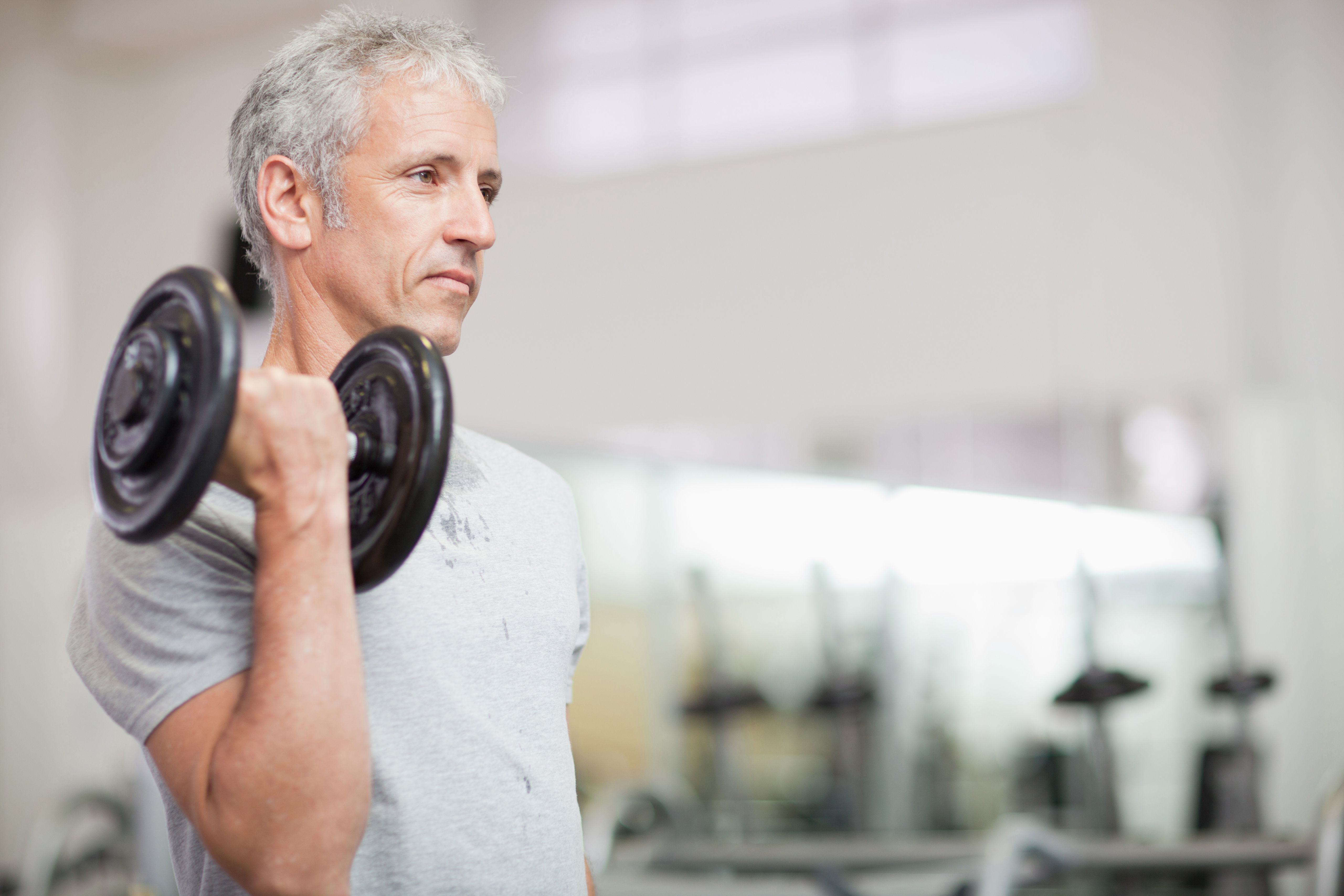 Portrait of man holding barbell in gymnasium