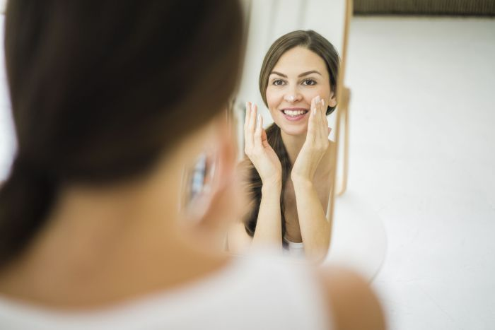 Portrait of woman looking at her mirror image in the morning creaming her face