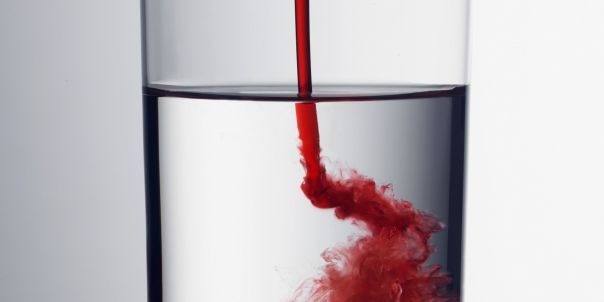 Red liquid pouring into glass indoors