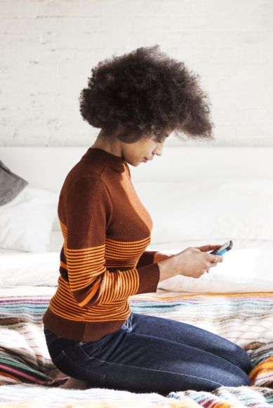 Side view of woman using smart phone while kneeling on bed at home