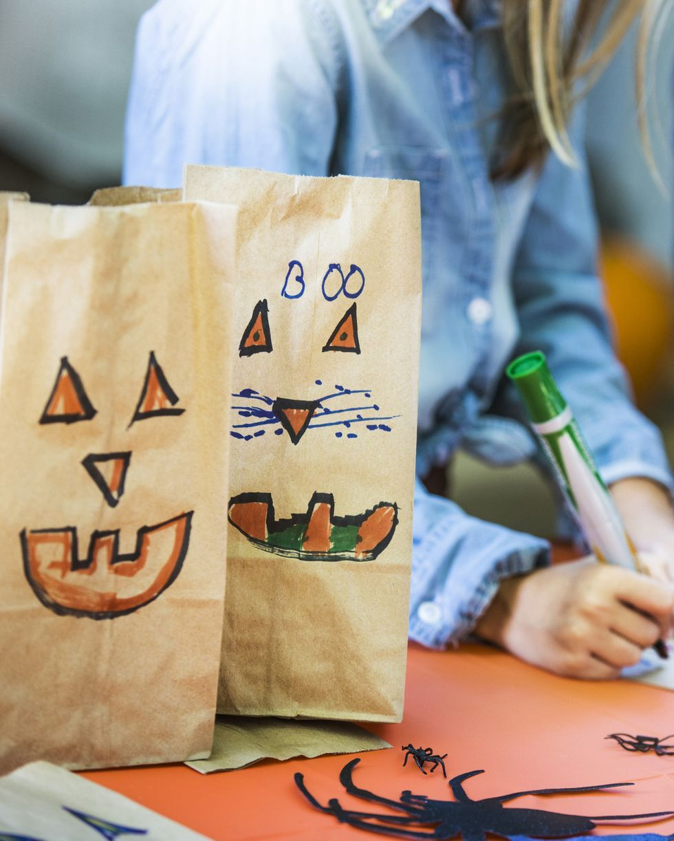 smiley faces on paper bags by siblings making art at table during halloween party